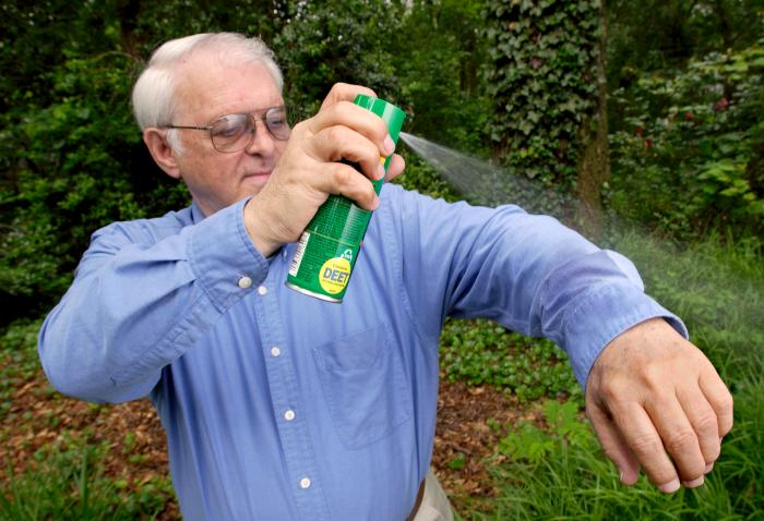 Man using bug repellant