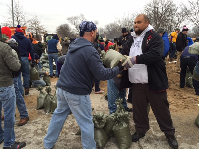 Volunteers load sand bags for the River Des Peres Levee