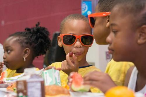 "Young Child wearing orange ""No Kid Hungry"" sun glasses"